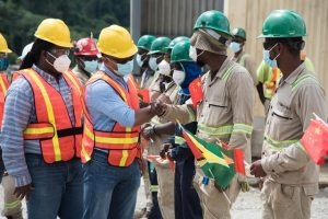 Minister of Natural Resources, Vickram Bharrat, greeting a Guyanese employee at the Aurora Gold Mine. Permanent Secretary at the Ministry, Joslyn McKenzie, is pictured at left
