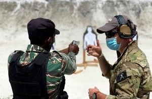A member of the seventh battalion of the U.S. Army Special Forces instructor explains one of the many concepts at the shooting range to a GDF rank during training