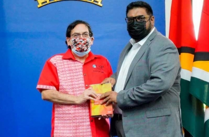 Professor Misir presents copies of his books to President, Vice-President